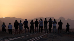 People staring at sunset in a dusty rocky environment