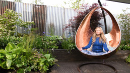 Woman meditating in a copper egg shaped garden chair